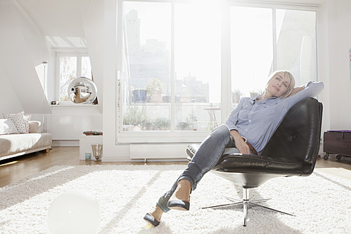 Germany, Bavaria, Munich, Woman relaxing on chair in living room - RBYF000283