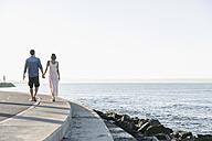 Spain, Mid adult couple walking along coast - WESTF019013