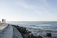Spain, Mid adult couple walking along coast - WESTF019016
