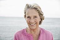 Spain, Senior woman smiling at Atlantic ocean - WESTF019048