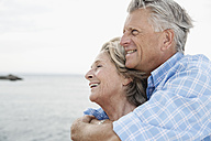 Spain, Senior couple embracing at harbour, smiling - WESTF019051