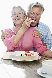Spain, Senior couple having lunch, smiling - WESTF019063