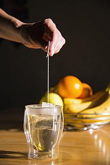 Human hand preparing tea, bowl of fruits in background - ABAF000370