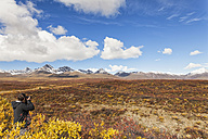 USA,  Alaska, Tourist taking photograph of Alaska Range in autumn - FOF004431