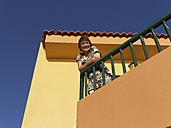 Spain, Woman leaning on balcony of Tres Palmeras apartments at La Gomera - SIE003008