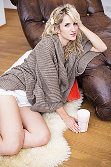 Portrait of young woman sitting on fur carpet with coffee - VRF000095
