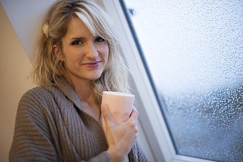 Young woman standing at window with coffee, smiling, portrait - VRF000093