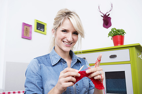 Young woman knitting with red yarn, smiling, portrait - VRF000098