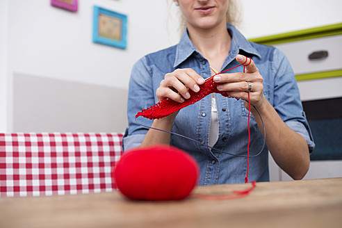 Young woman knitting with red yarn - VRF000101