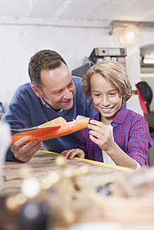 Germany, Leipzig, Father and son repairing toy plane - BMF000573