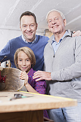 Germany, Leipzig, Grandfather, father and son repairing skateboard - BMF000582