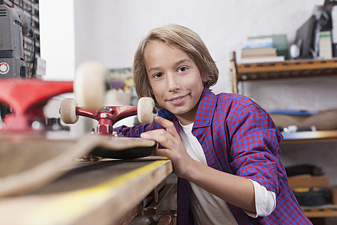 Germany, Leipzig, Boy repairing skateboard, portrait - BMF000585