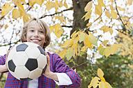 Germany, Leipzig, Boy playing football under autume tree - BMF000624