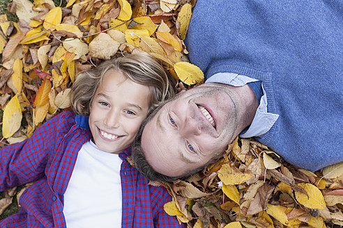 Germany, Leipzig, Father and son lying on leaves, smiling - BMF000630