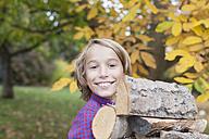 Germany, Leipzig, Boy holding firewood, smiling - BMF000638