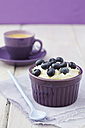 Bowl of milk rice pudding with blueberries and coffee in background - ECF000159
