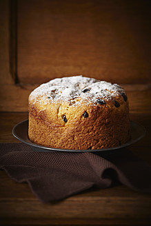 Panettone cake with cranberries and icing sugar on plate - ECF000162