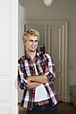 Germany, Berlin, Young man standing beside door, smiling - SKF000983