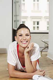 Germany, Berlin, Young woman lying on floor, smiling - SKF000995