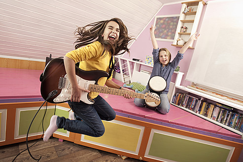 Girls jumping while playing guitar and drums - RNF001094