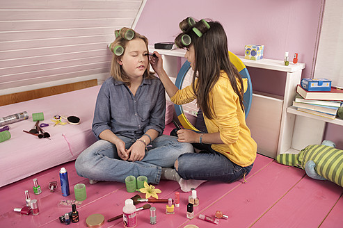 Girls with hair rollers applying make up, smiling - RNF001069