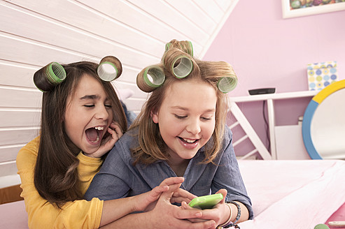 Girls with hair rollers lying and watching smartphone, smiling - RNF001079