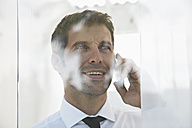Spain, Businessman talking on mobile phone, smiling - PDYF000346