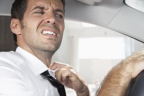 Spain, Dispressed businessman driving car - PDYF000358
