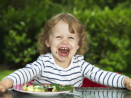 Germany, Duesseldorf, Girl sitting outside and eating spinach, smiling, portrait - STKF000047