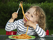 Germany, Duesseldorf, Girl sitting outside and eating noodles - STKF000048
