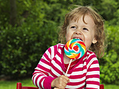 Germany, Duesseldorf, Girl sitting outside and eating lollipop - STKF000054