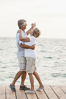 Spain, Senior couple dancing on jetty at the sea - JKF000013