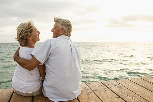 Spain, Senior couple embracing at the sea - JKF000025