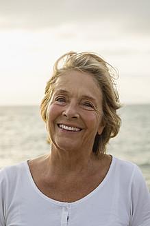 Spain, Senior woman at the sea, smiling - JKF000031