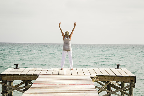 Spain, Senior woman exercising on jetty at the sea - JKF000040