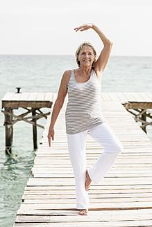 Spain, Senior woman doing yoga on jetty at the sea - JKF000043