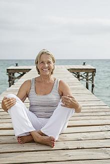 Spain, Senior woman sitting on jetty at the sea - JKF000046