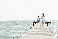 Spain, Girl and boy running on jetty at the sea - JKF000073