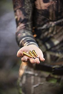 USA, Texas, Young woman holding Caliber 30-30 cartridges - ABAF000415