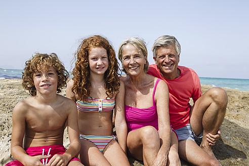 Spain, Grandparents with grandchildren sitting at beach, smiling, portrait - JKF000090