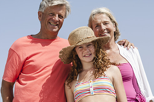 Spain, Grandparents with granddaughter at beach, smiling, portrait - JKF000093