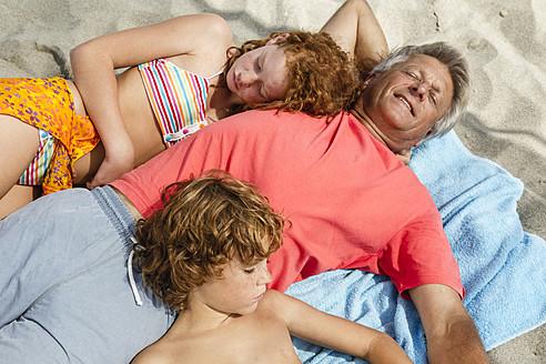Spain, Grandfather and grandchildren relaxing on beach - JKF000096