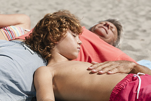 Spain, Grandfather and grandson relaxing at beach - JKF000108