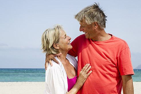 Spain, Senior couple romancing at beach, smiling - JKF000114