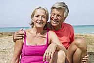 Spain, Senior couple sitting on rock at beach, smiling - JKF000117