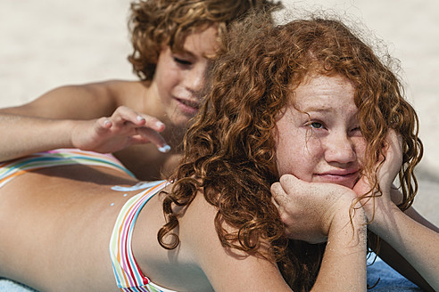 Spain, Brother drawing on sisters back with suncream - JKF000126