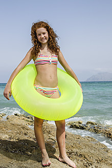 Spain, Girl with swim ring on beach, smiling - JKF000135