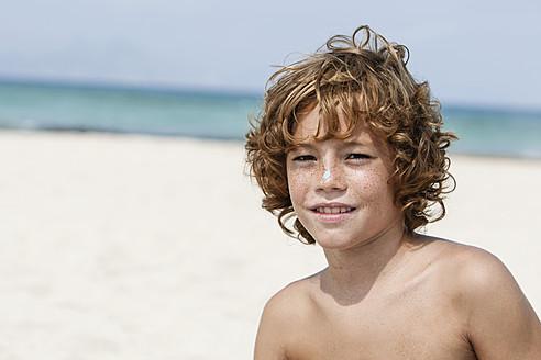 Spain, Boy sitting on beach, smiling - JKF000141