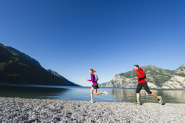 Italy, Mid adult couple jogging by Lake Garda - MIRF000511