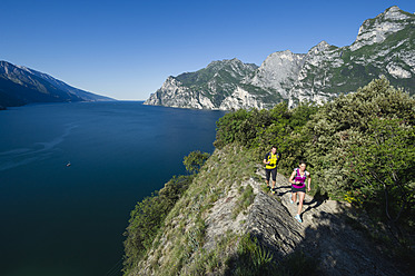 Italy, Mid adult couple jogging by Lake Garda - MIRF000514